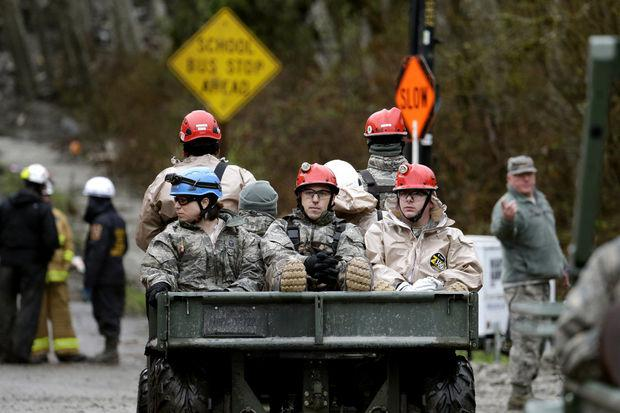 Searchers are brought in along Highway 530 to the scene of a deadly mudslide Saturday, March 29, 2014, in Oso, Wash.