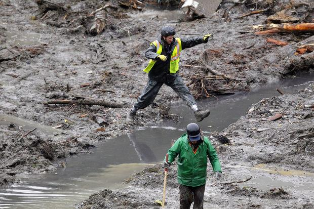 A searcher leaps across a small creek at the scene of a deadly mudslide Saturday, March 29, 2014, in Oso, Wash.