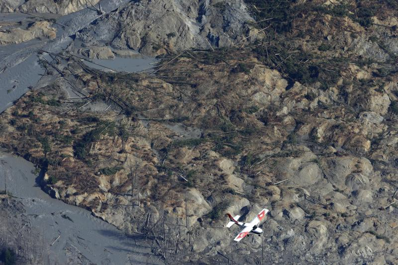 A Civil Air Patrol plane flies over the massive mudslide that killed at least eight people and left dozens missing as shown in this aerial photo, Monday, March 24, 2014, near Arlington, Wash.