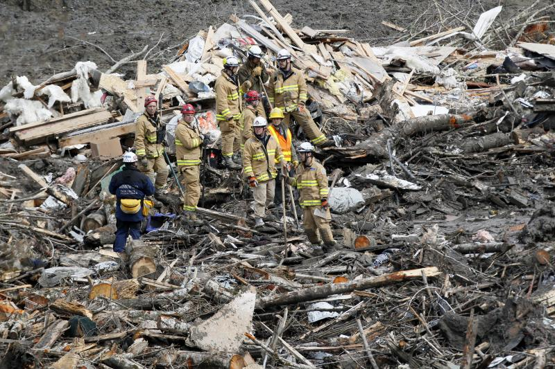 Searchers stand in a pile of debris at the scene of a deadly mudslide that covers the road, Wednesday, March 26, 2014, in Oso, Wash.