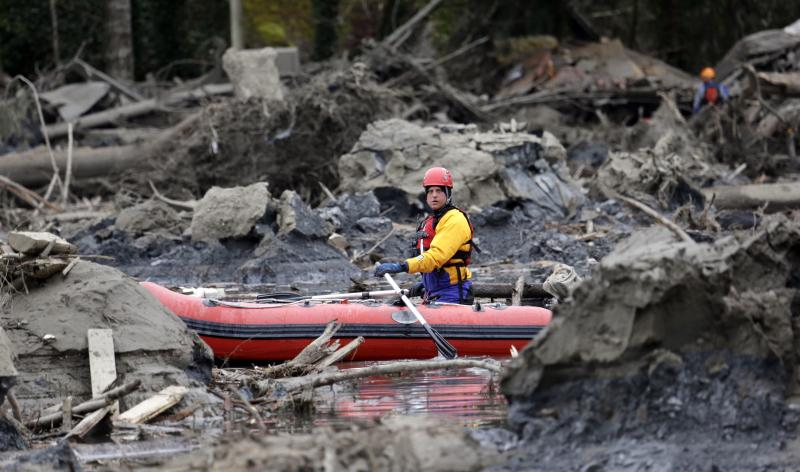 A searcher uses a small boat to look through debris from a deadly mudslide Tuesday, March 25, 2014, in Oso, Wash.