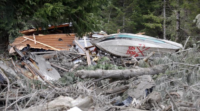 The remains of a house and of a boat lie with other debris following a deadly mudslide, Tuesday, March 25, 2014, in Oso, Wash.