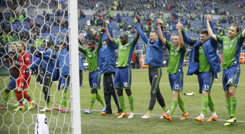Seattle Sounders players and other team personnel celebrate after the Sounders beat Sporting Kansas City 1-0 in an MLS soccer match, Saturday, March 8, 2014, in Seattle.