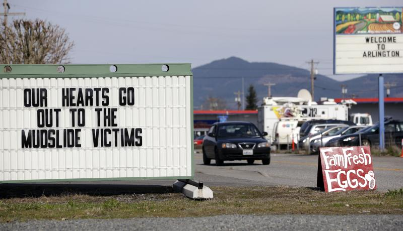 A sign outside a coffee shop references a deadly mudslide that happened two days earlier, Monday, March 24, 2014, in Arlington, Wash.