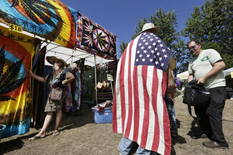 FILE - In this Aug. 16, 2013 file photo, a man wears an American flag as he walks past a vendor selling tie-dyed products at the first day of Hempfest in Seattle.