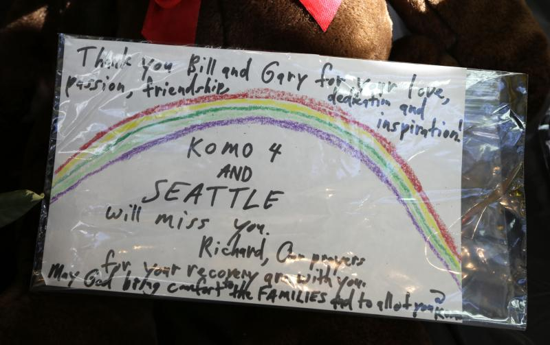 A hand-written message is shown amidst flowers, candles, and cards on display Wednesday, March 19, 2014, in Seattle at a growing memorial in the lobby of KOMO-TV.
