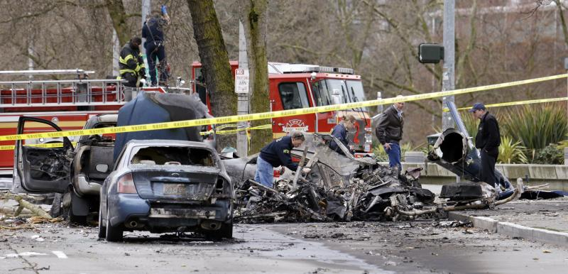 Investigators look through the charred wreckage of a news helicopter and two vehicles after the chopper crashed into a city street near the Space Needle, Tuesday, March 18, 2014, in Seattle.