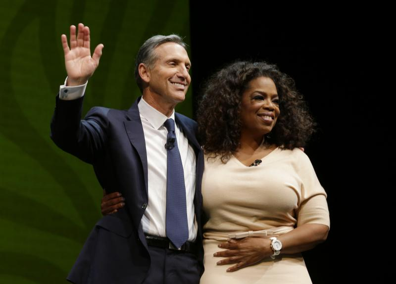 Howard Schultz, left, chairman and CEO of Starbucks Coffee Company, stands with Oprah Winfrey, right, after they announced their partnership to offer Teavana Oprah Chai tea, Wednesday, March 19, 2014, at Starbucks' annual shareholders meeting in Seattle.