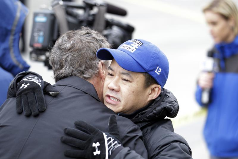 KOMO assignment editor Norm Mah, right, gets a hug as he works at the scene of the crash of a KOMO news helicopter Tuesday, March 18, 2014, in Seattle.