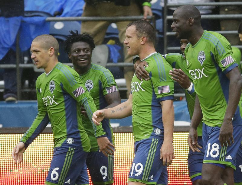 Seattle Sounders forward Chad Barrett (19) center, celebrates with teammates Osvaldo Alonso, left, Obafemi Martins, (9), and Djimi Traore, (18) after Barrett kicked a goal against Sporting Kansas City.