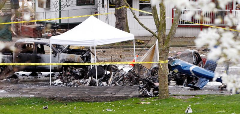 Caution tape surrounds the charred wreckage of a news helicopter and two vehicles after the chopper crashed into a city street near the Space Needle.