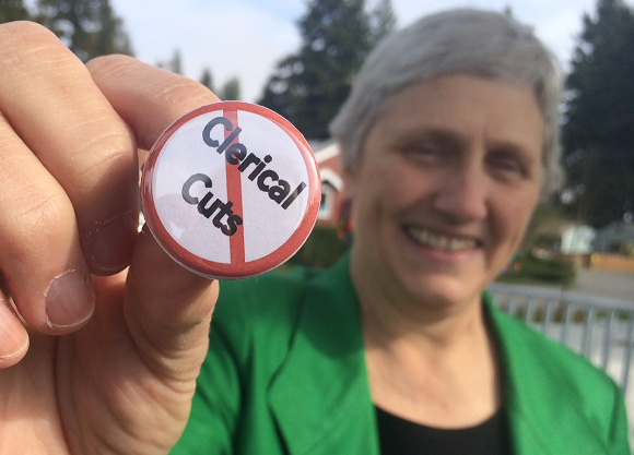 Mary Smith, an administrative secretary at Seattle's Ingraham High School, shows the button she wore last week to protest planned staffing cuts in district schools. Ingraham staff voted to reject their building budget.