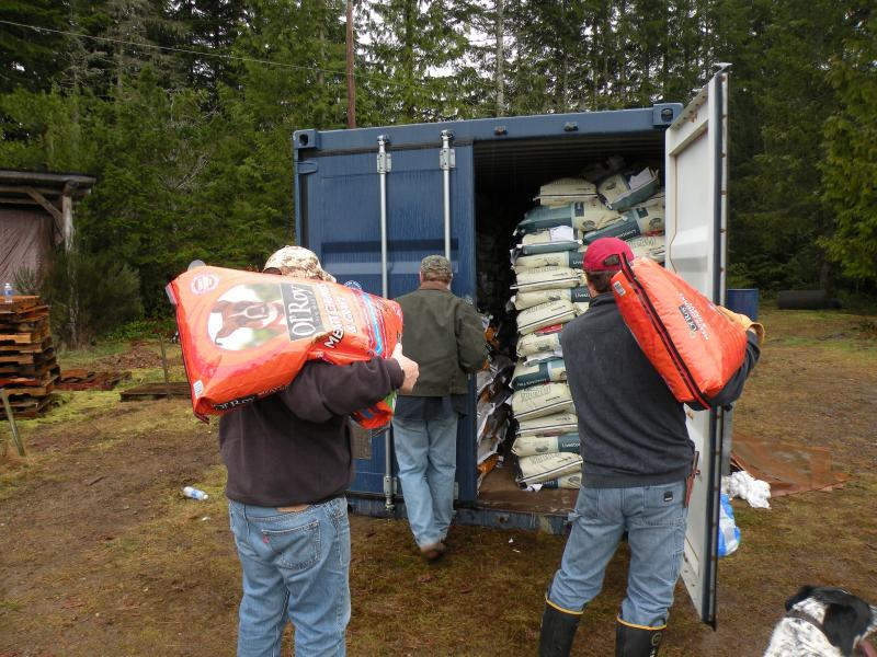 Donated cat, dog, chicken and livestock feed gets piled into two shipping containers at the Darrington Rodeo Grounds. Organizers say they're asking residents to clear out their barns to store donations.