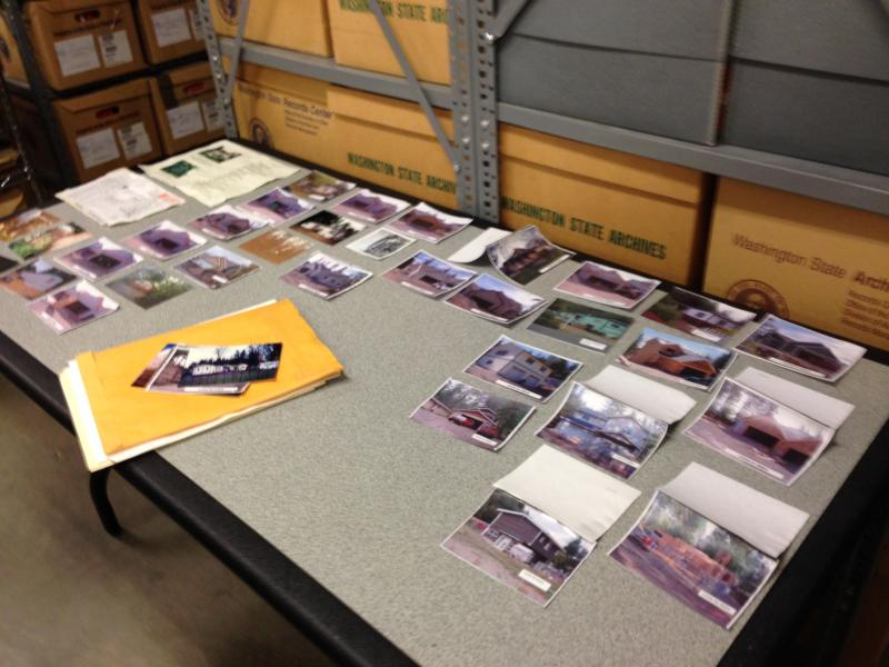 Photographs are spread out on a table to dry after a burst sink line sent water into a section of the Washington State Archives.