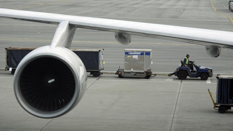 A baggage handler drives a cart below a United Airlines 747-400, at San Francisco International Airport in San Francisco, Wednesday, Feb. 23, 2011.