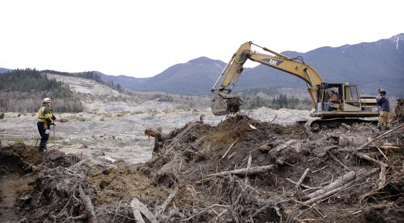 Workers move debris at the scene of a deadly mudslide, torn off from the hill at upper left almost two weeks earlier, Thursday, April 3, 2014, in Oso, Wash.