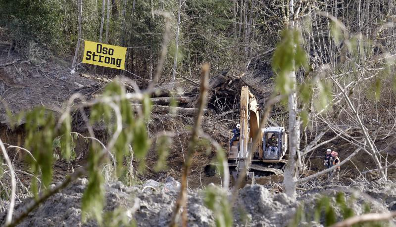Searchers work with heavy equipment near the edge of a deadly mudslide, Wednesday, April 2, 2014, in Oso, Wash.