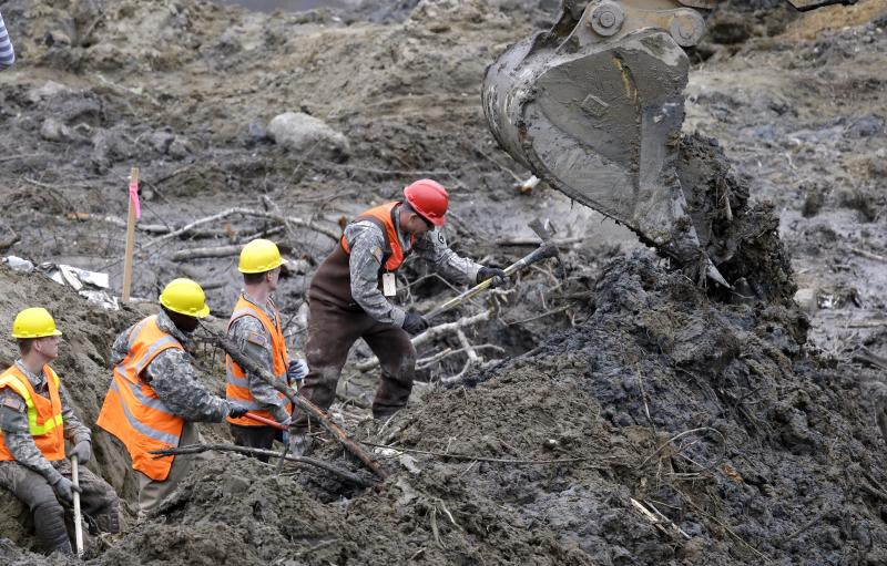Workers use hand tools next to heavy equipment at the scene of a deadly mudslide nearly two weeks earlier nearby, Thursday, April 3, 2014, in Oso, Wash.