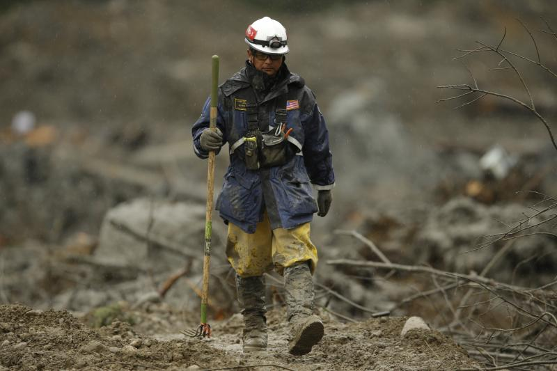 A search worker walks with a tool Wednesday, April 16, 2014, as the search continues for the remaining missing victims of the massive deadly mudslide that hit the community of Oso, Wash. on March 22, 2014.