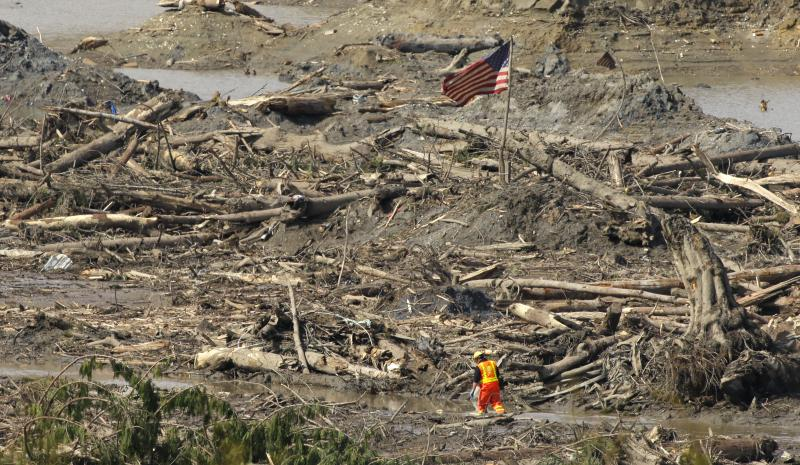 A searcher walks through a channel of water as a flag flies in the debris field Monday, March 31, 2014, near Darrington, Wash., at the site of the massive mudslide that hit the nearby community of Oso,Wash. on March 22, 2014.