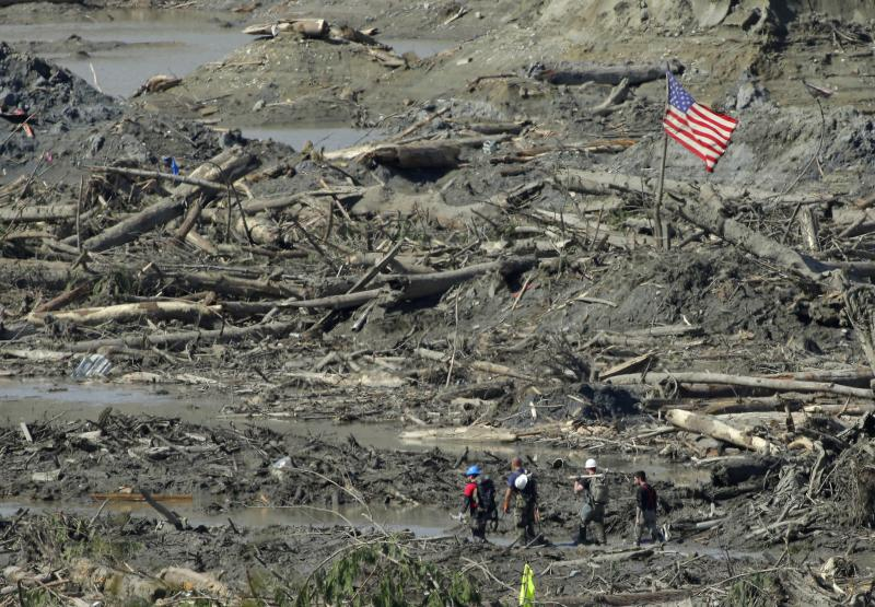 Workers carrying hand tools and shovels walk past a U.S. flag Tuesday, April 1, 2014, near Darrington, Wash., in the debris field of the deadly mudslide that hit the community of Oso,Wash. on March 22, 2014.