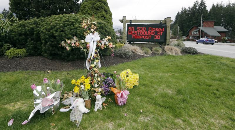 A road sign advising the closure of Highway 530 stands near a small display of flowers and a cross Tuesday, April 15, 2014, in Darrington, Wash.