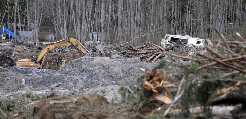 A demolished recreational vehicle lies in a debris field at the scene of a deadly mudslide nearly two weeks earlier nearby, Thursday, April 3, 2014, in Oso, Wash.