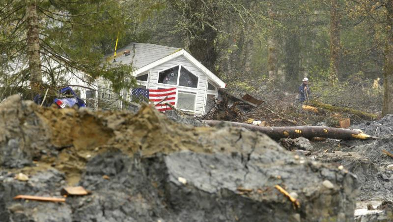 In this Wednesday, April 16, 2014, photo, a flag hangs on one of two buildings pushed together near the edge of the massive deadly mudslide that hit the community of Oso, Wash., on March 22, 2014.