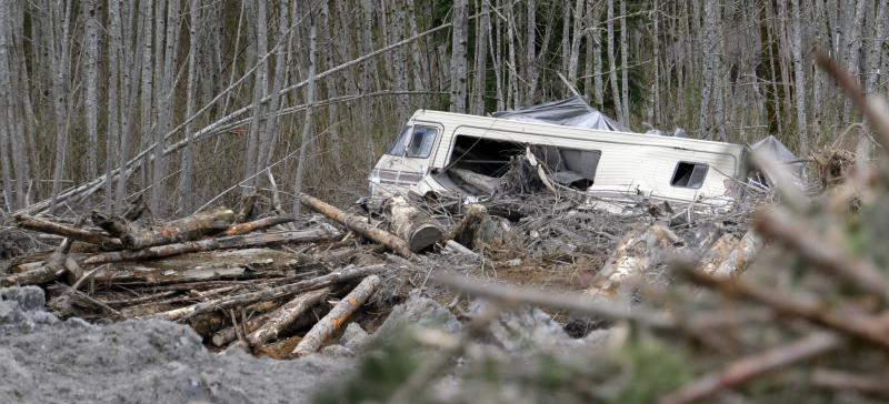 A demolished recreational vehicle lies near the edge of a debris field at the scene of a deadly mudslide, Thursday, April 3, 2014, in Oso, Wash.