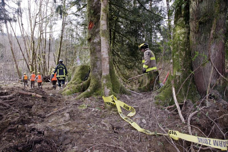 Emergency workers walk at the scene of a deadly mudslide that happened over a week earlier, Wednesday, April 2, 2014, in Oso, Wash.
