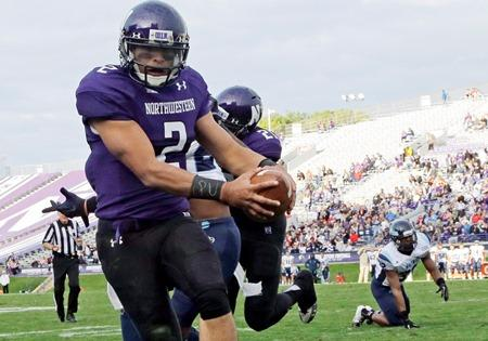 "In this Sept. 21, 2013 file photo, Northwestern quarterback Kain Colter wears APU for ""All Players United"" on wrist tape. Colter is the face of the union movement."