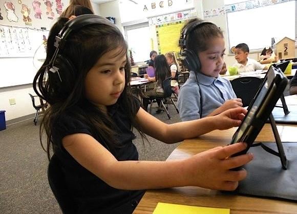 A preschooler at Tacoma's Stafford Elementary uses an application on a school-owned iPad that allows her teacher to track her progress.