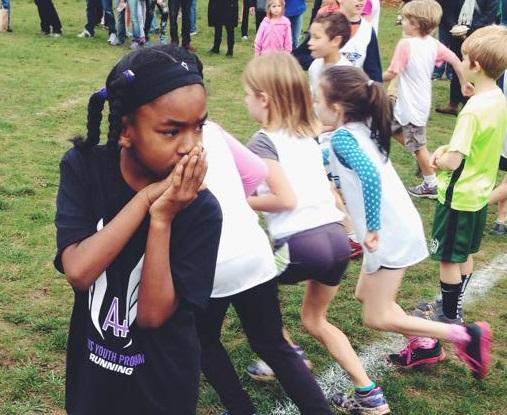 A student in the A PLUS Youth Program gets ready to run a race. The organization offers after-school mentorship and academic tutoring in addition to youth sports programming.