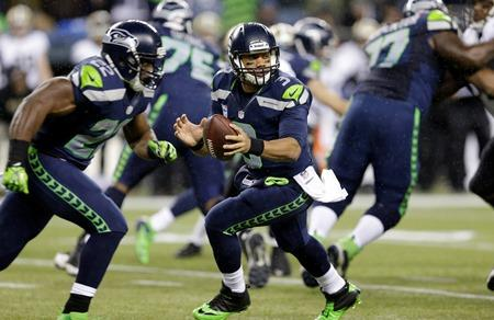 Seahawks quarterback Russell Wilson drops back as Seahawks' Robert Turbin runs a pattern against the New Orleans Saints, Monday, Dec. 2, 2013, in Seattle.