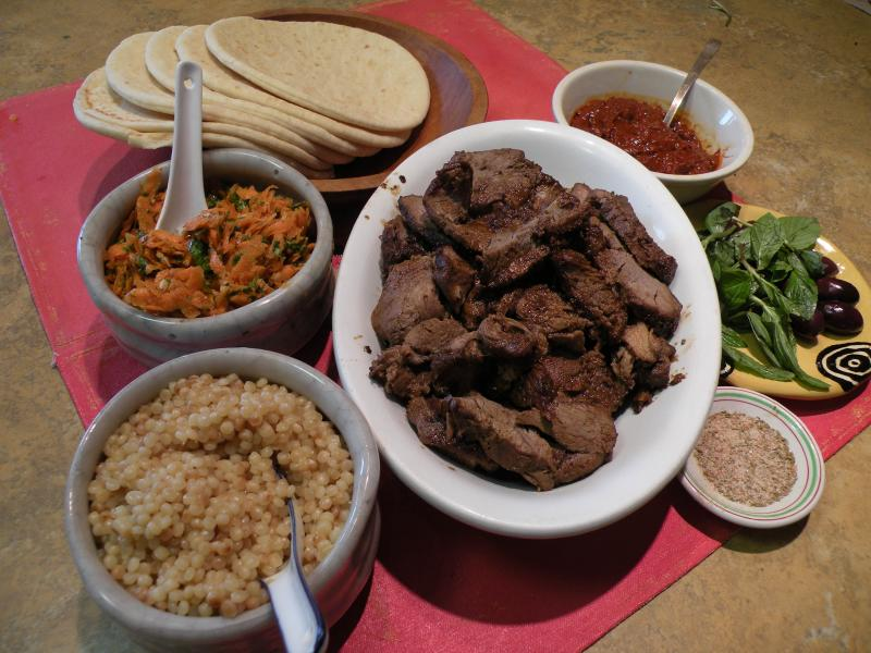 Clockwise from top: Flatbread, harissa, mint and olives,cumin/salt dipping mix, Mechoui lamb, couscous, Moroccan carrot salad.