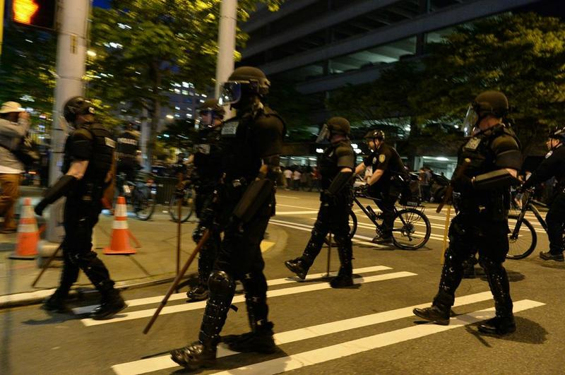 Police in riot gear are seen following the marchers.