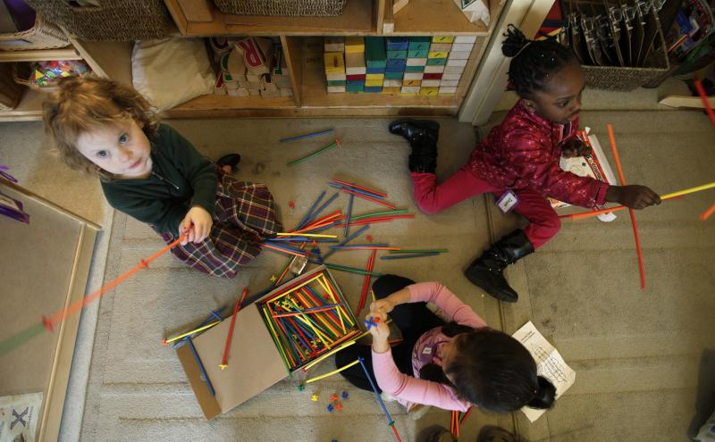 "FILE - In this April 5, 2012, photo, pre-school students Molly Kiniry, 4, left, Imani Workcuff, 4, upper right, and Lyvia Pham, 4, lower right, build ""castles"" with building sticks at the Refugee and Immigrant Family Center in Seattle."