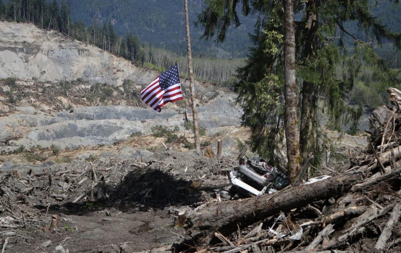 A destroyed vehicle and a flag, at half staff, are seen from a one-lane road around the Highway 530 slide area Tuesday, April 29, 2014, near Oso, Washington.