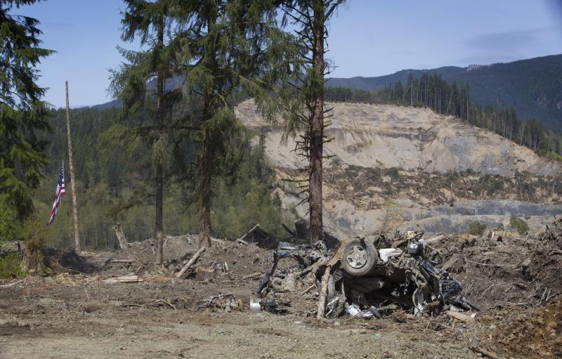 A destroyed vehicle and a flag, at half staff, are seen from a one-lane road around the Highway 530 slide area Tuesday, April 29, 2014, near Oso, Wash.