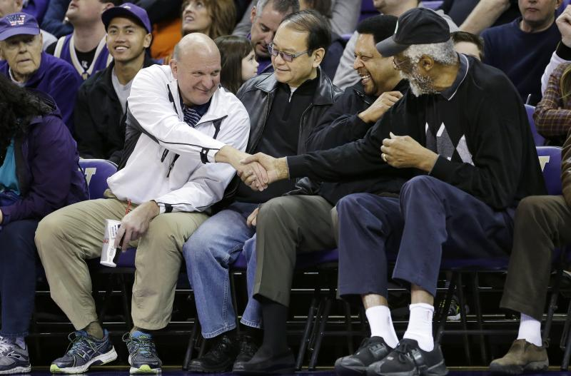 "FILE - In this Jan. 25, 2014, photo, then-Microsoft CEO Steve Ballmer, left, shakes hands with former NBA players Bill Russell, right, and ""Downtown"" Freddie Brown as Omar Lee looks on during an NCAA college basketball game."