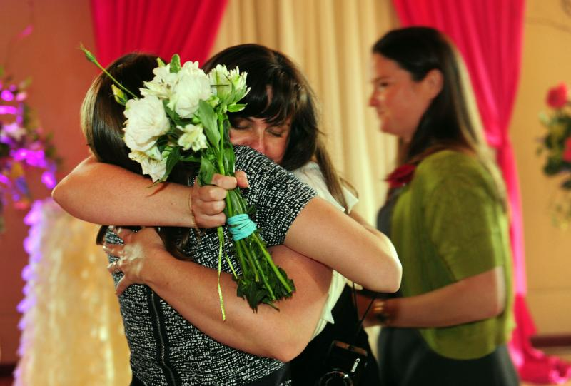 Julia Fraser hugs a family member after getting married as Jessica Rohrbacher, right, walks behind after get married at the Melody Ballroom in Portland, Ore., on Monday, May 19, 2014.