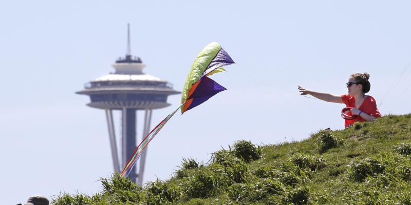Beth Lehinger pulls in a kite under clear skies atop a hill in Seattle's Gasworks Park and in view of the Space Needle as the afternoon temperature neared 80 degrees Wednesday, April 30, 2014.