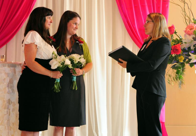 Julia Fraser, left, and Jessica Rohrbacher get married by Celebrant Holly Pruett, right, at the Melody Ballroom in Portland, Ore., on Monday, May. 19, 2014.
