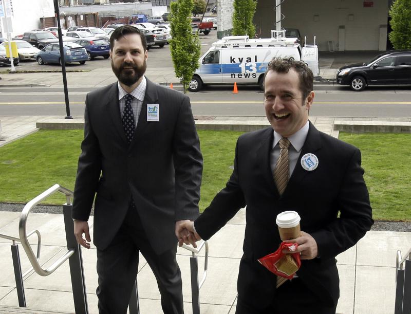 FILE - Plaintiffs Ben West, left, and Paul Rummell walk hand-in-hand in to federal court where a federal judge is scheduled to hear oral arguments in two cases challenging Oregon's ban on same-sex marriage in Eugene, Ore., Wednesday, April 23, 2014.