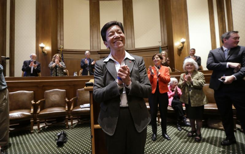 New Washington state Supreme Court Justice Mary Yu is applauded by current court members behind as she acknowledges the gallery after being sworn in to the bench Tuesday, May 20, 2014, in Olympia, Wash.