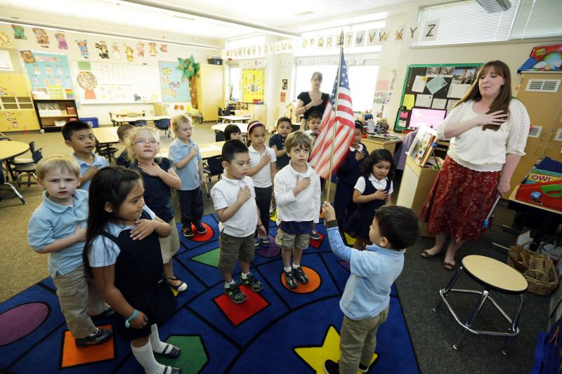 In this April 30, 2014 photo, children in Erin Kling's, right, pre-kindergarten class recite the Pledge of Allegiance at the start of the school day at Stafford Elementary School in Tacoma, Washington.