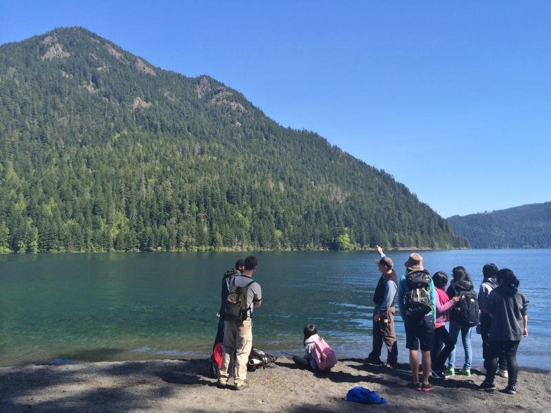 NatureBridge camp educator Adam Logan points out the features of Pyramid Mountain, across Crescent Lake from the campsite where Rainier Beach High School students are staying this week.