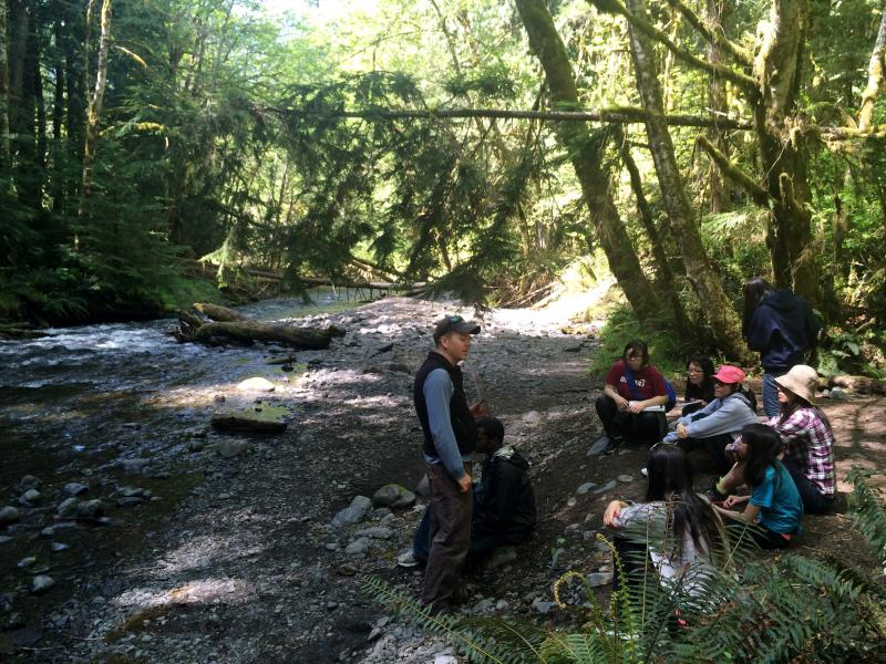 Rainier Beach students listen to NatureBridge camp educator Adam Logan discuss experimental design along the banks of Barnes Creek.