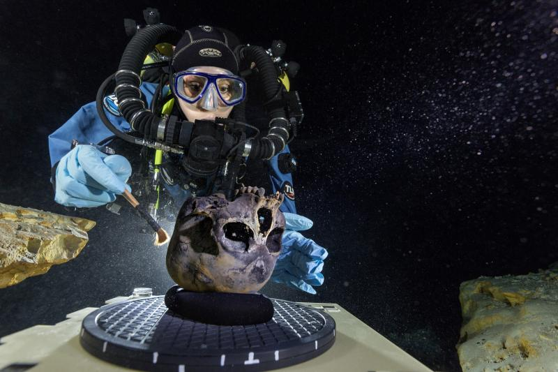 Diver Susan Bird working at the bottom of Hoyo Negro, a large dome-shaped underwater cave   on Mexico's Yucatán Peninsula. She carefully brushes the human skull found at the site while  her team members take detailed photographs.