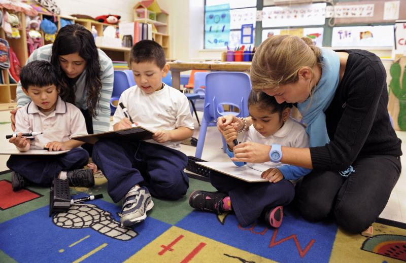 Pre-kindergarten teaching assistant Mirna Ayala, left, and teacher Laura Amling, right, work with their 3-year-old students to draw an alphabet shape at Powell Elementary School in Washington, D.C.